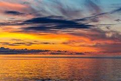 Härlig brännhet solnedgånghimmel på stranden fotografering för bildbyråer