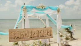 Härlig bröllopbåge på stranden TräID-Märke med namnen av bruden och brudgummen bröllop för tappning för klädpardag lyckligt arkivfilmer