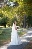 Härlig bröllopbukett av blommor i händer av den unga bruden Royaltyfria Bilder