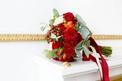 Härlig bröllopbukett av röda rosor och guld- vigselringar i den vita inre Arkivfoto