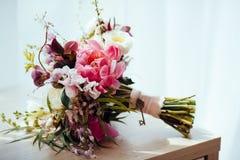 Härlig bröllopbukett som ligger på tabellen, blommor, rosor, brud- detalj för peones arkivbilder