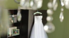 Härlig bröllopsklänning som hänger i rummet arkivfilmer