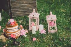 Härlig bröllopstårta med blommor, stearinljus och garneringar utomhus royaltyfria foton