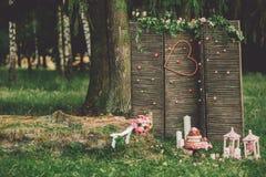 Härlig bröllopstårta med blommor, stearinljus och garneringar utomhus fotografering för bildbyråer