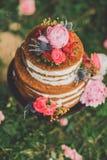 Härlig bröllopstårta med blommor, utomhus Två nivåer arkivfoton