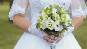 Härlig brud- bukett i händer av den unga bröllopsklänningen för iklädd vit för brud stock video