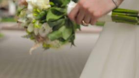 Härlig brud- bukett i händer av den unga bröllopsklänningen för iklädd vit för brud arkivfilmer