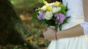 Härlig brud- bukett i händer av den unga bröllopsklänningen för iklädd vit för brud Stäng sig upp av stor grupp av ny vit lager videofilmer