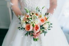 Härlig brud- bukett med vita rosor och persikapioner i händer för en brud i den vita klänningen Bröllopmorgon Närbild Arkivbilder