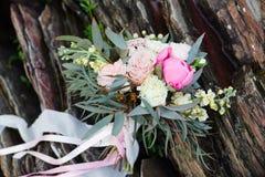 Härlig brud- bukett som ligger på stenarna En bukett för ceremonin för bröllop för flicka` s härliga delikata blommor Royaltyfri Foto