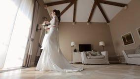 Härlig brud i bröllopsklänningen som går till fönstret i hotellrummet lager videofilmer