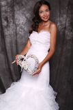 Härlig brud i bröllopsklänningen som rymmer dekorativ hjärta Arkivbild