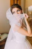 Härlig brud i den vita bröllopsklänningen som döljer hennes framsida bak skyla Kvinnlig stående i den brud- kappan för förbindels Arkivfoton