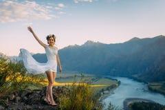 Härlig brud i den vita korta klänningen som poserar över ekologiskt landskap av berg och floden med blå molnig himmel fotografering för bildbyråer