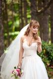 Härlig brud i elegant vit klänninginnehavbukett arkivbild