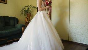 Härlig brud i en bröllopsklänning med buketten