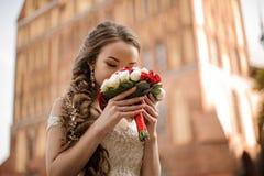 Härlig brud i en bröllopsklänning med en flätad trådfrisyr som sniffar en bukett av nya rosor royaltyfria bilder