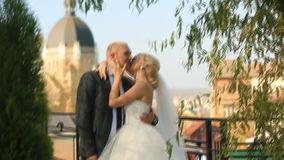 Härlig brud i en bröllopsklänning och en brudgum som ler och kysser lyckligt på den kyrkliga bakgrunden stock video