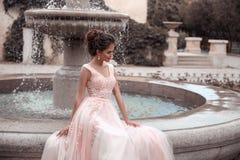 Härlig brud i rosa bröllopsklänning Utomhus- romantisk stående av den attraktiva brunettkvinnan med frisyren i studentbalklänning royaltyfri bild