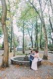 Härlig brud i siden- sammanträde för bröllopkappa på knä av hennes älska brudgum, medan han vilar vid den torkade springbrunnen i Royaltyfria Bilder