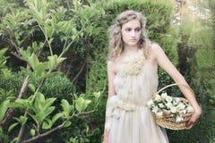 Härlig brud i trädgård i bröllopkappan, klänning Arkivfoton