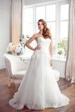 Härlig brud i ursnygg bröllopsklänning inomhus Gifta sig mode Arkivfoton