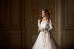 Härlig brud med buketten i lyxig inre i den barocka stilen Royaltyfria Bilder