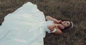 Härlig brud med den fantastiska klänningen som lägger ner i gräset stock video
