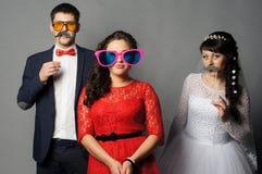 Härlig brud med hennes flickvänner som poserar på studion Royaltyfri Foto