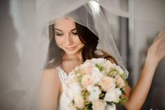 Härlig brud med stilfullt smink i den vita klänningen royaltyfri fotografi