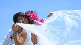 Härlig brud och brudgum på stranden Skyla brudar som fladdrar beautifully i vinden stock video