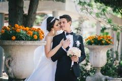 Härlig brud och brudgum som poserar i en gård av en slott Arkivfoto