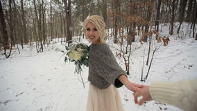 Härlig brud och följa hennes brudgum i vinterskog stock video