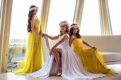 Härlig brud och två brudtärnor i gula liknande klänningar tillsammans i en havsrestaurang Royaltyfria Bilder