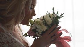 Härlig brud som luktar bröllopbuketten lager videofilmer