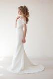 Härlig brud som poserar den bröllopfrisyren och klänningen arkivfoton