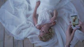 Härlig brud som poserar i hennes bröllopsklänning lager videofilmer