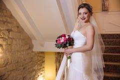 Härlig brud som poserar med en bukett av blommor som ler och står på trappan Den obligatoriska bröllopsklänningen Fotografering för Bildbyråer