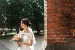 Härlig brud som poserar nära den röda väggen av den gamla gotiska kyrkan royaltyfria bilder