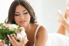 Härlig brud som rymmer den bröllops- buketten Arkivbild