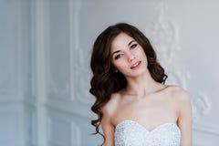 härlig brudstående Bröllopgarnering och klänning, vit bakgrund Royaltyfri Foto