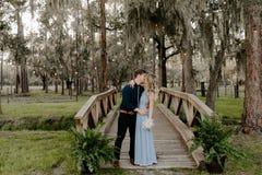 Härlig brudtärnakvinna i blå klänning och bukett med hennes datum på en formell berömhändelse för gifta sig parti utanför i trät royaltyfri bild