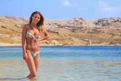 Härlig brunbränd flicka i ett bikinianseende i ett vatten Arkivbilder