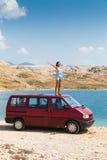 Härlig brunbränd flicka i ett blått klänninganseende på ett tak av den röda skåpbilen Arkivbild