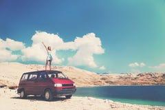Härlig brunbränd flicka i ett blått klänninganseende på ett tak av den röda skåpbilen och fördelande armar Arkivfoton
