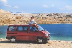 Härlig brunbränd flicka i ett blått klänningsammanträde på ett tak av den röda skåpbilen Fotografering för Bildbyråer