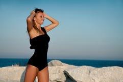 Härlig brunbränd kvinna i svart baddräkt på stranden Royaltyfria Foton