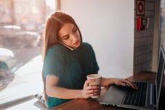 Härlig brunett genom att använda bärbara datorn i kafé Den unga attraktiva kvinnan gör plan inför framtiden och att sitta framme  arkivbilder