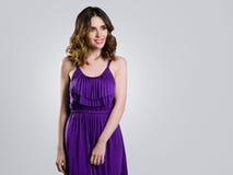 Härlig brunett i den violetta klänningen Royaltyfri Foto