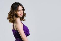Härlig brunett i den violetta klänningen Royaltyfri Fotografi